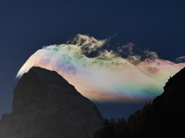 Eine Wolke hinter einem Berg mit perlmut Farben.