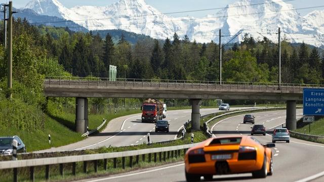 Autos fahren auf der Autobahn A1 unter einer Eisenbahnbrücke durch.