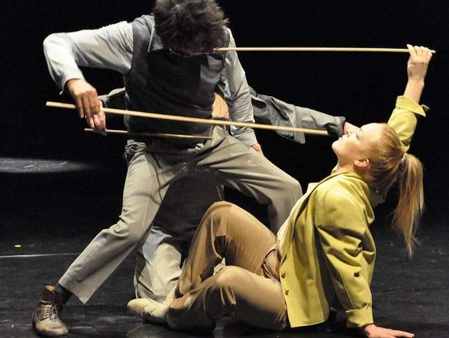 Zwei Tänzer kämpfen mit Stöcken.