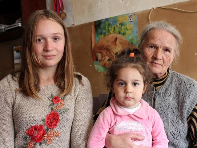 Grossmutter mit Enkelinnen im Raum.