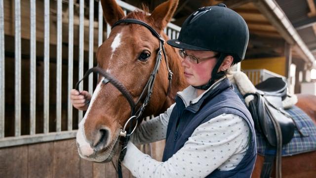 Frau mit Reithelm steht neben einem Pferd