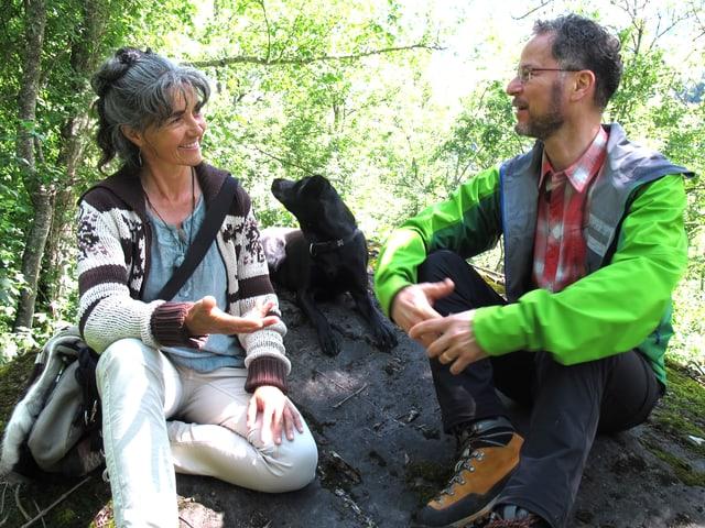 Eine Frau und ein Mann sitzen diskutierend auf einem Stein im Wald