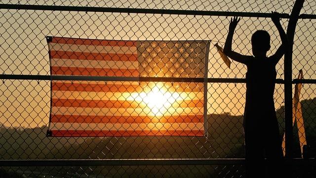 Ein Junge steht vor einem Zaun. Am Zaun hängt eine USA-Flagge.