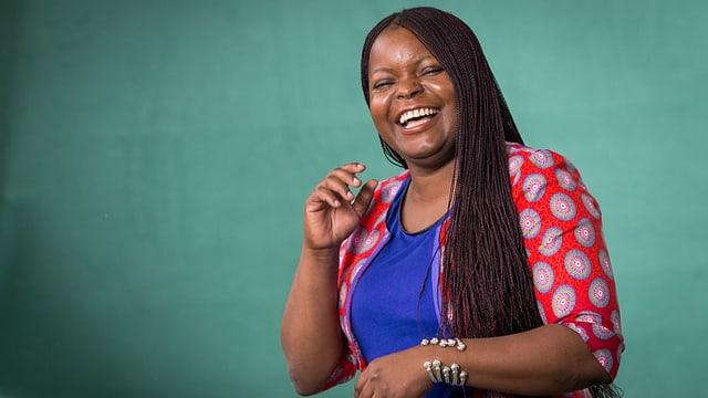 Petina Gappah lacht. Sie trägt ein blaues und ein rotes Oberteil.