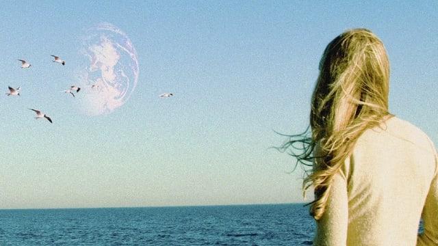 Marlin steht am Ufer und blickt in den Himmel, wo sich die zweite Erde abbildet.