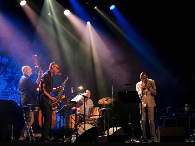 Eine Momentaufnahme während eines Jazzkonzerts. Die dunkle Bühne ist mit einzelnen, farbigen Scheinwerfern beleuchtet. Die Mitglieder der Band «Still Dreaming» mit Kontrabass, Schlagzeug, Trompete und Saxophon stehen dicht beieinander und spielen ihre Instrumente. Sie schauen einander nicht an, und bilden doch eine Einheit.