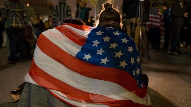 Zwei Personen in eine US-Flagge eingehüllt