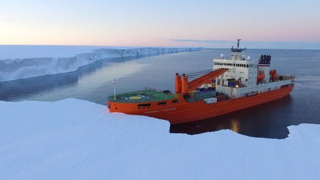 Ein grosses Schiff vor einer Schneelandschaft.