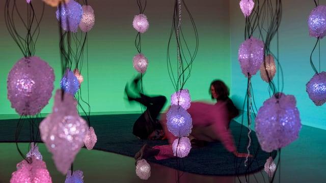 Von der Wand hängen Drähte mit pinken, kristallförmigen LED-Leuchten