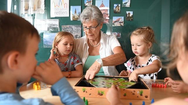 Ältere Frau sitzt zwischen Schulkindern.
