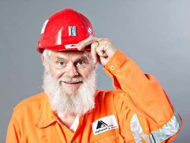 Alter Mann in orangefarbenem Anzug und rotem Helm auf dem Kopf.