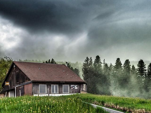 Dunkle Wolken mit vielen Pollen in der Luft. Im Vordergrund ist ein Bauernhaus.