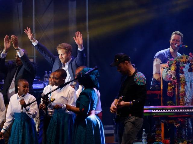 Prinz Harry steht auf der Bühne und hält die Hände hoch. Im Hintergrund sitzt Chris Martin von Coldplay am Piano.