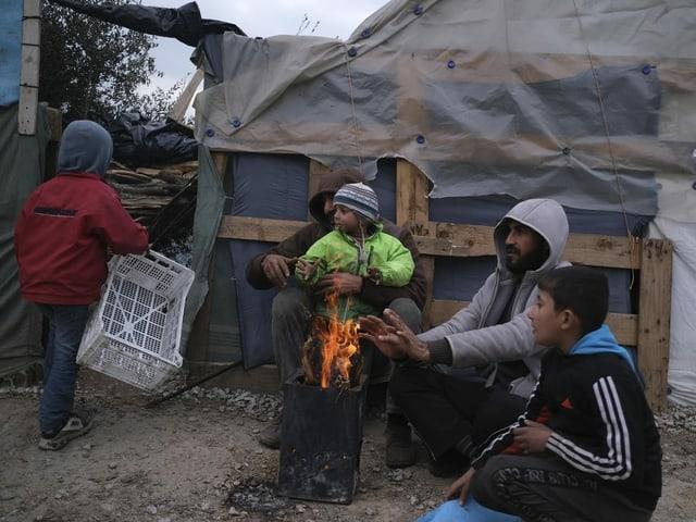 Jugendliche wärmen sich an einem Feuer.