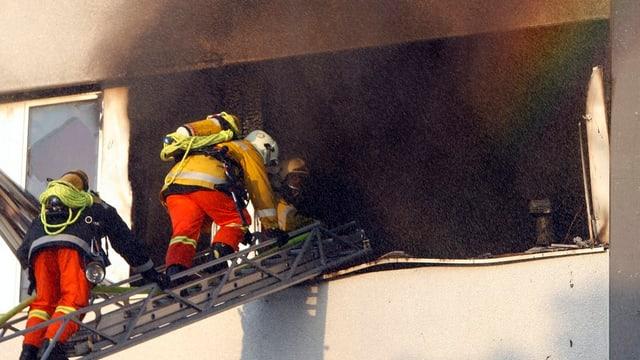 Feuerwehrleute steigen in ein brennendes Gebäude.