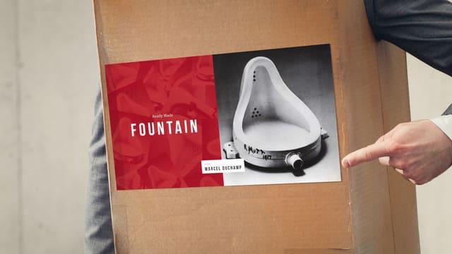 Hand zeigt auf ein Bild von Duchamps Urinal, welches auf einen Karton geklebt ist.