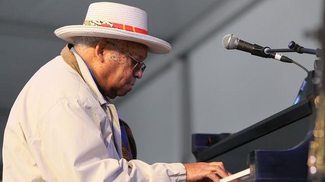 Mann mit Hut auf einer Bühne an einem Klavier