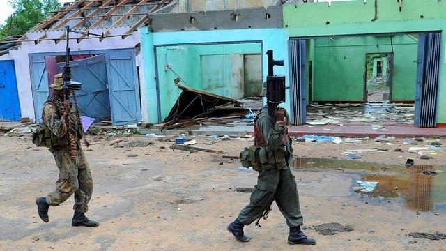Soldaten vor zerstörten Häusern.