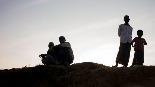 Umrisse von Männern, die auf einem Hügel stehen.