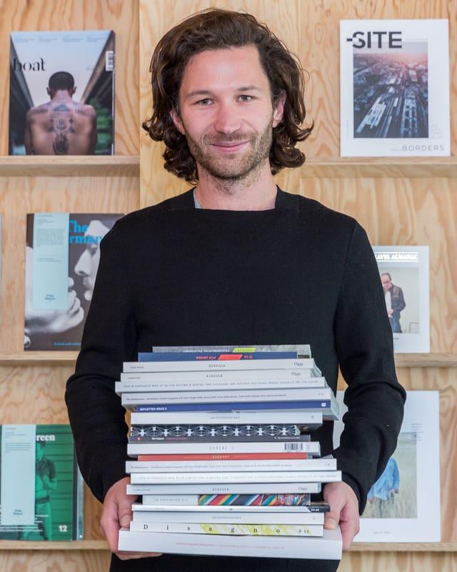Ein junger Mann posiert mit einem Stapel Zeitschriften in den Händen vor einem Bücherregal.