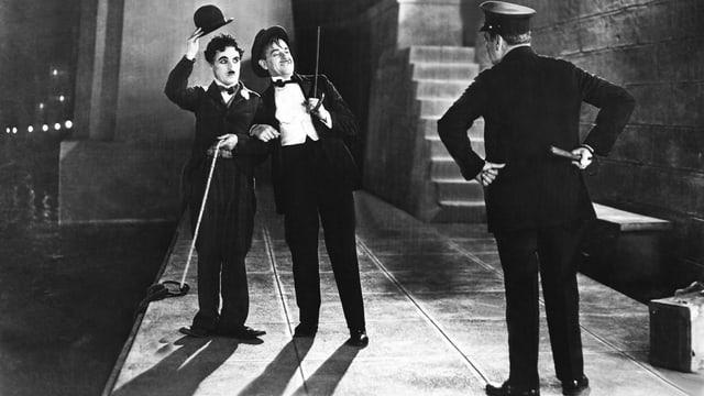 Schwarzweiss-Filmszene: Chaplin mit Melone uns STock grüsst zusammen mit einem betrunken aussehneden Mann einen Polizisten.