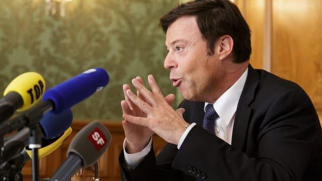 Christoph Mörgeli spricht sitzend in mehrere Mikrofone.