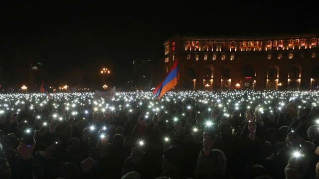 Tausende Lichter von Smartphones, mittendrin eine Fahne.