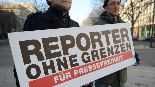 Zwei Männer halten ein Schild von Reporter ohne Grenzen.