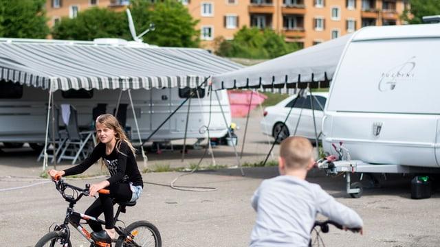 Kinder auf Velos fahren vor Wohnwagen herum