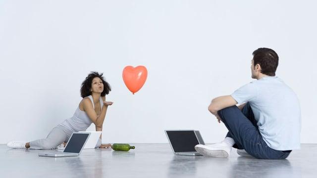 Eine Frau pustet einen Herz-Luftballon in Richtung eines Mannes.