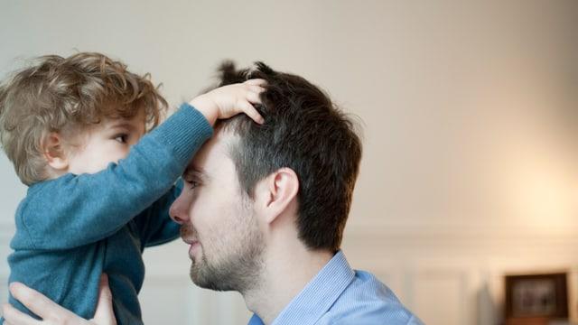 Ein Kind greift seinem Vater mit den Händen in die Haare.