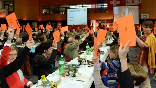 An der Delegiertenversammlung der CVP 2013 halten Frauen orange Stimmzettel in die Höhe.