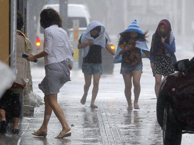 Japaner suchen Schutz vor dem Regen