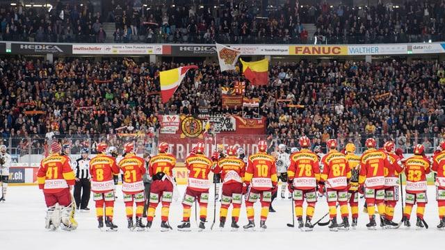 Eishockeyspieler auf dem Eis, vor ihnen Tribüne mit Fans