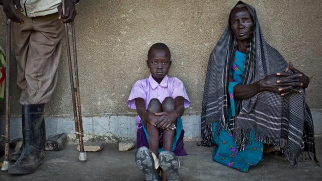 Ein Mädchen und eine Frau warten im Südsudan am Boden sitzend auf medizinische Hilfe.