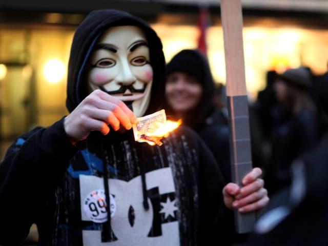 Maskierter Mann verbrennt Dollarnote.