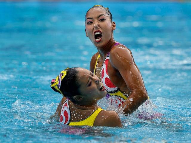 Schwimmerinnen im Wasser, verzerrte Gesichter.