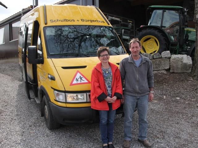 """Eine Frau und ein mann stehen vor einem kleinen Bus mit der Aufschrift """"Schulbus + Bürgerbus""""."""