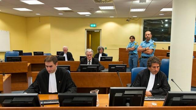 Karadzic sitzt im Verhandlungssaal, ebenfalls anwesend zwei uniformierte Polizisten und mehrere Juristen.