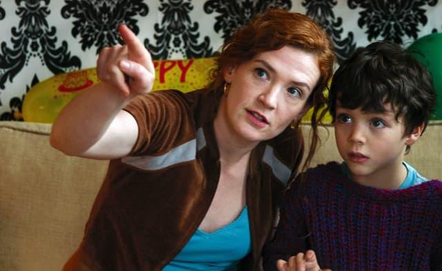 Eine Frau zeigt einem kleinen Jungen etwas.