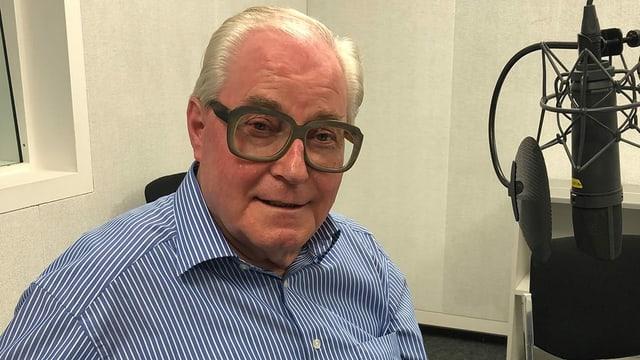 Ein Mann mit Hornbrille vor einem Mikrofon in einem Radiostudio.