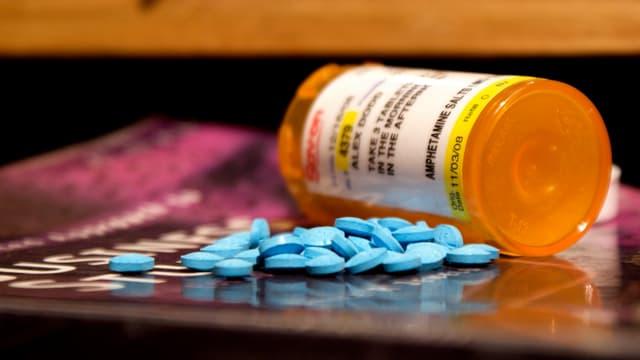 Eine orange Pillendose mit Addreall-Pillen davor.