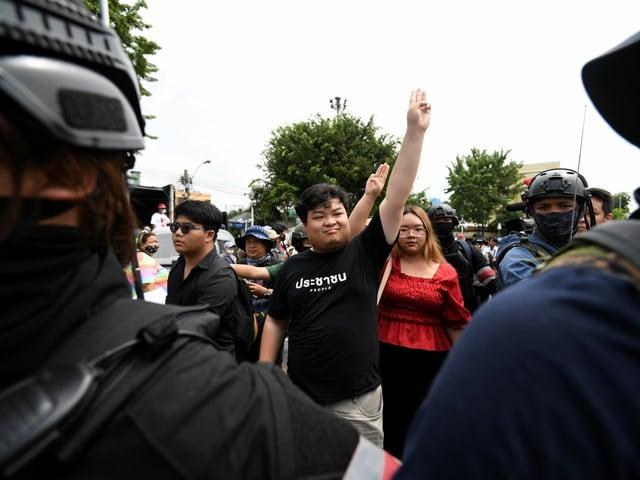 Zwei junge pro-demokratische Studierendenführende strecken ihre drei Finger in die Luft.