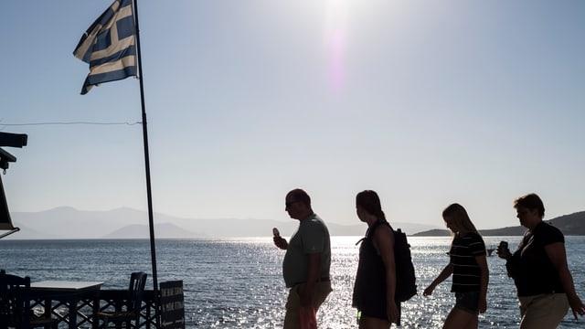 Turists a la riva da la mar en la Grezia.