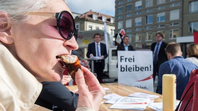 Eine Frau beisst in eine Bratwurst, im Hintergrund stehen SVP-Wahlkampfleiter.