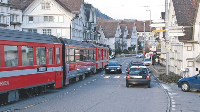 Strasse mit rotem Zug und Autos im Gegenverkehr