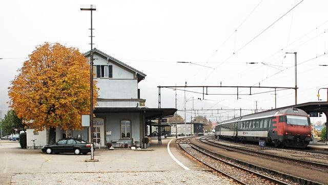 Bahnhofgebäude und rechts davon ein Zug im Bahnhof Oensingen.
