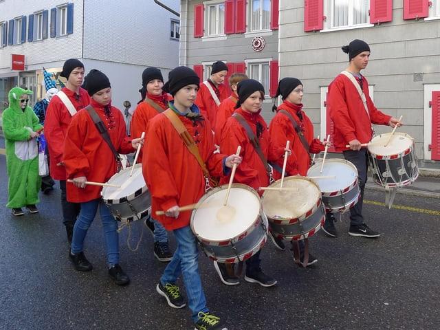 Eine Gruppe junger Tambouren zieht in roten Gewändern durchs Dorf.