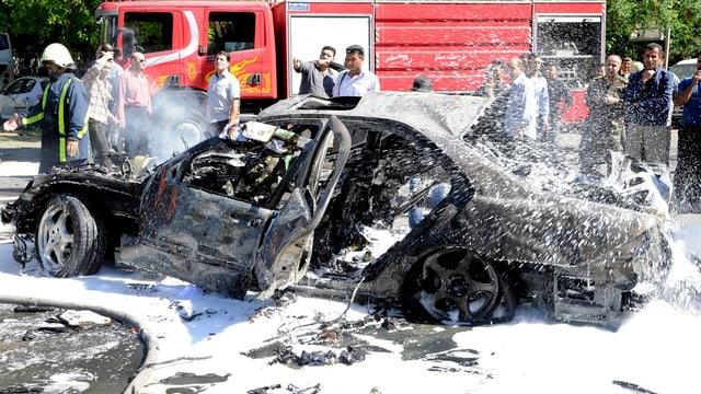 Die Feuerwehr löscht ein völlig ausgebranntes und zerstörtes Auto