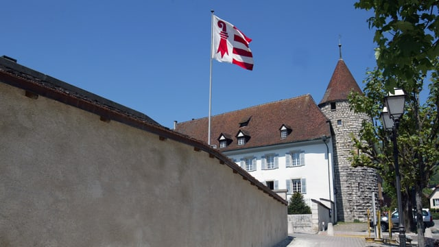 Totale auf ein Gebäude mit einem Turm und einer Jura-Flagge.